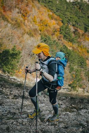 rival rivals rivalry season: Yalta, Russia - November 2, 2015: male athlete goes to mountain behind him a small child during Mountain marathon Vertical kilometre AI-Petri