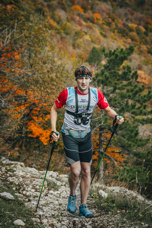 kilometre: Yalta, Russia - November 2, 2015:young male athlete is on a mountain trail with walking sticks during Mountain marathon Vertical kilometre AI-Petri
