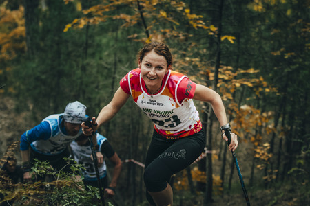 "Yalta, Rusland - 2 november 2015: glimlachende jonge vrouw met wandelstokken tijdens Mountain marathon ""Vertical kilometer AI-Petri"" Redactioneel"
