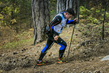 kilometre: Yalta, Russia - November 2, 2015: male athlete goes to mountain behind him a small child during Mountain marathon Vertical kilometre AI-Petri