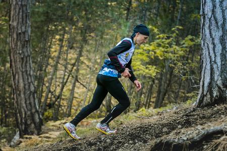 rival rivals rivalry season: Yalta, Russia - November 2, 2015: male athlete climbs a steep hill in woods during Mountain marathon Vertical kilometre AI-Petri