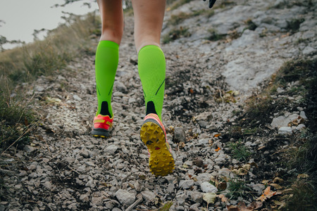 closeup of feet running girls on a mountain trail.fitness adventure and exercising in mountains. woman running uphill marathon in compression socks