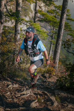 rivals rival rivalry season: Yalta, Russia - November 4, 2015: male runner goes uphill through pine forest during mountain marathon Tauris