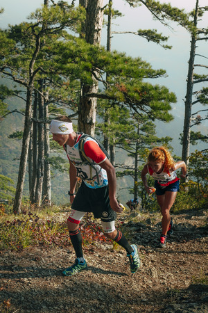 rival rivals rivalry season: Yalta, Russia - November 4, 2015: girl athlete with walking sticks going uphill during mountain marathon Tauris Editorial