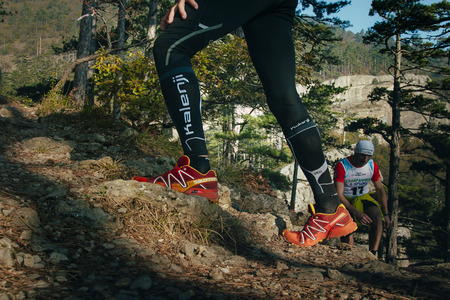 rival rivals rivalry season: Yalta, Russia - November 4, 2015: closeup feet of male runner running uphill on a mountain trailduring mountain marathon Tauris