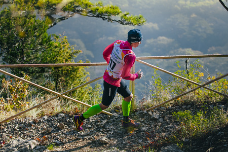 rivals rival rivalry season: Yalta, Russia - November 4, 2015: young woman athlete running on mountain trail. in background of mountain valley during mountain marathon Tauris