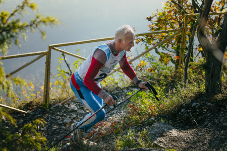 rival rivals rivalry season: Yalta, Russia - November 4, 2015: elderly male runner with nordic walking poles mountain trail up during mountain marathon Tauris