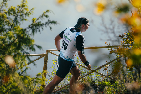 rival rivals rivalry season: Yalta, Russia - November 4, 2015: man athlete running on mountain trail. in background of mountain valley during mountain marathon Tauris