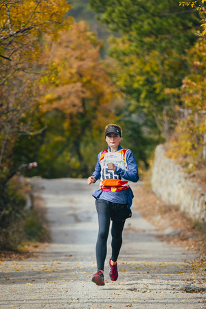 rivals rival rivalry season: Yalta, Russia - November 4, 2015: young woman runs across road in autumn forest during mountain marathon Tauris