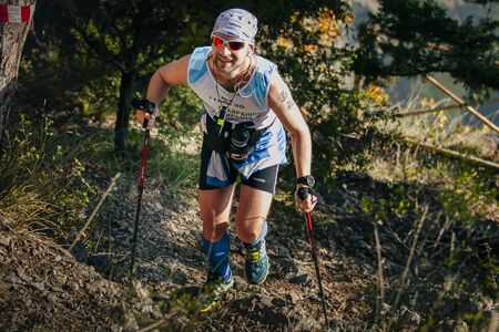 isotonic: Yalta, Russia - November 4, 2015: male athlete in forest is Hiking traill with nordic walking poles during mountain marathon Tauris