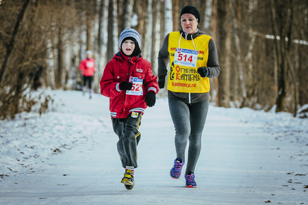 rival rivals rivalry season: Ekaterinburg, Russia - November 14, 2015: family, a son and mother run together winter woods during Urban winter marathon