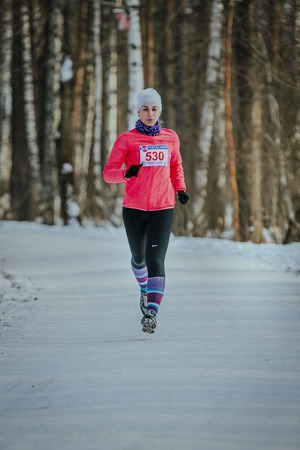 rival rivals rivalry season: Ekaterinburg, Russia - November 14, 2015: young woman trail running in winter forest during Urban winter marathon