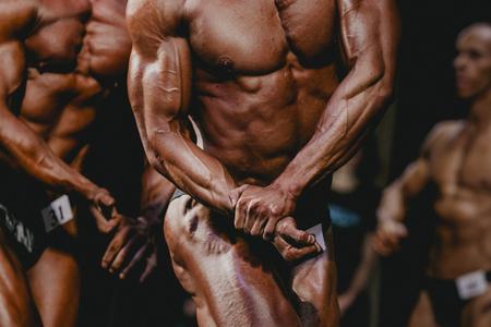 bodybuilder: Chelyabinsk, Russia - October 3, 2015: athletes bodybuilders are straining biceps side of arm during Championship of Chelyabinsk region on bodybuilding, bodyfitness and fitness