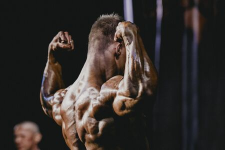 dorsi: performance athlete bodybuilder to competition. demonstration of biceps your arms from behind Editorial