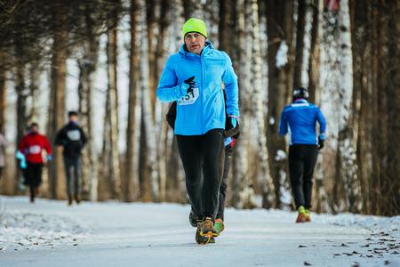rival rivals rivalry season: Ekaterinburg, Russia - November 14, 2015: man middle-aged runner runs on road snowy Park during Urban winter marathon