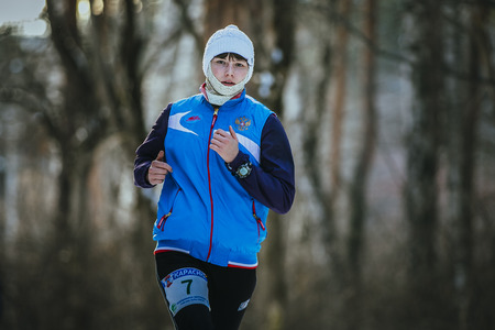 rival rivals rivalry season: Ekaterinburg, Russia - November 14, 2015: beautiful young woman running in winter forest during Urban winter marathon Editorial