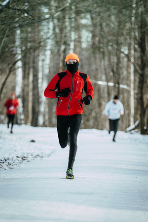 rival rivals rivalry season: young male jogger running through a snowy Park alley in winter Stock Photo