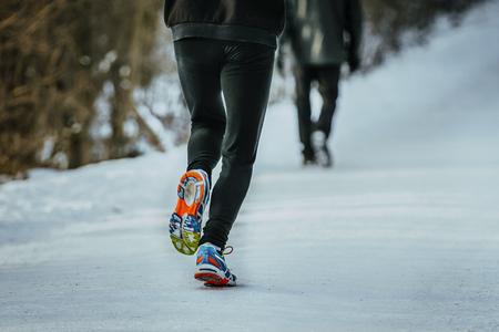 rivals rival rivalry season: closeup legs man athlete running on snow in Park in winter