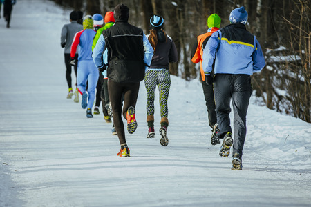 group young people running together snowy trail in winter Park. rear view 스톡 콘텐츠