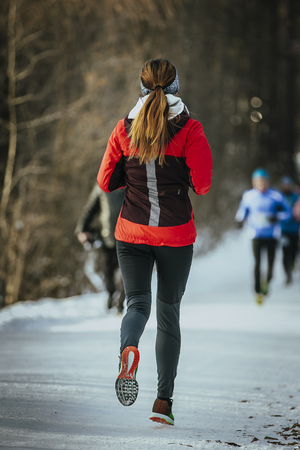 girl in sportswear: young woman runner running on snow-covered alley in a winter Park. rear view Stock Photo