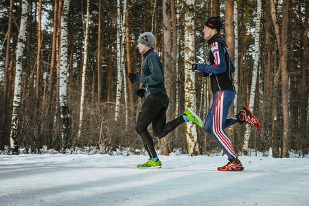 synchronously: Ekaterinburg, Russia - November 14, 2015: two men athletes run synchronously through snowy woods side view during Urban winter marathon