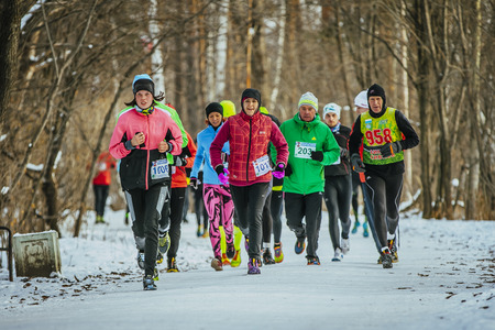 people in action: Ekaterinburg, Russia - November 14, 2015: group athlete men and women in bright winter clothes running along snowy path Park during Urban winter marathon Editorial