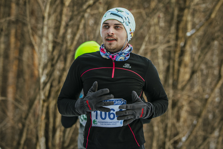 rival rivals rivalry season: Ekaterinburg, Russia - November 14, 2015: smiling young athlete in headphones runs through Park. cold weather during Urban winter marathon