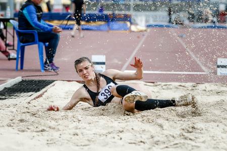 salto largo: bella atleta joven mujer en las competiciones de salto de longitud. salpicaduras de arena blanca en el aterrizaje. intento exitoso Foto de archivo