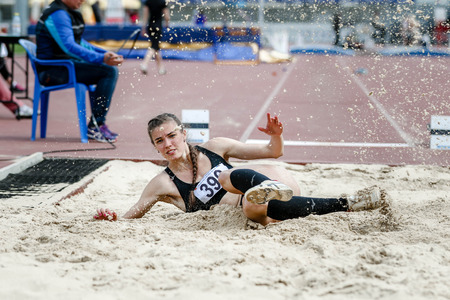beautiful young woman athlete at competitions long jump. splashes of white sand upon landing. successful attempt