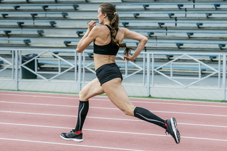 young woman athlete running sprint  track stadium in summer. beautiful and slim body. compression socks feet