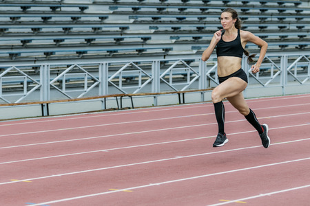 young beautiful woman runner running  sprint on track stadium. beautiful and slim body. exercises athletics in outdoors