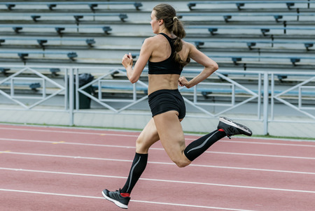 young girl running on track stadium sprint. athletics in summer. beautiful and slim body athletes