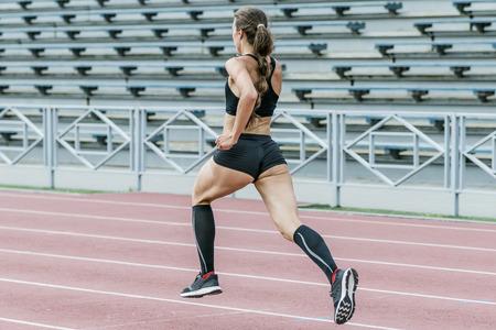 delgada mujer joven atleta corriendo en la pista del estadio. ejercicios para la velocidad de sprint. chica hermosa y sexy cuerpo