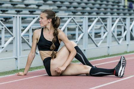 beautiful athletic girl doing exercises on flexibility. sexy and slim body. stretching legs sitting track stadium Stock Photo