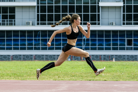girl athlete jumping triple jump in summer stadium. beautiful and young woman athlete