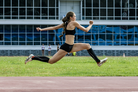 young woman athlete jumping triple jump in summer stadium. beautiful and sexy girl athlete