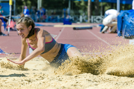 is long: young woman athlete jumping long jump at stadium. spray sand Stock Photo