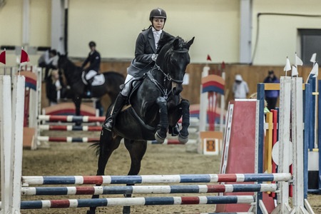 sports complex: Chelyabinsk, Russia - November 22, 2015: young woman rider horse overcomes obstacles sports complex indoors during Competitions Horse Show jumping Editorial