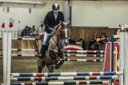 sports complex: Chelyabinsk, Russia - November 22, 2015: man athlete rider horse overcomes obstacles sports complex indoors during Competitions Horse Show jumping Editorial
