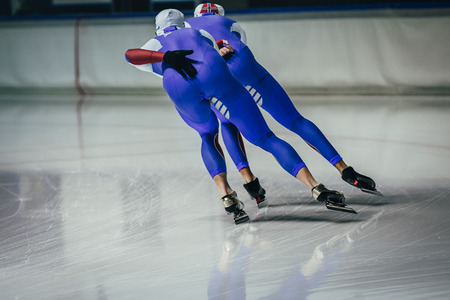 synchronous: young men athletes skater equally roll during warm-up before competitions in speed skating
