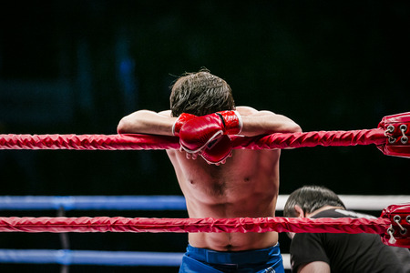 fighters: mixed martial arts fighter (MMA) stands in corner ring. lost fight. defeat of an opponent Stock Photo