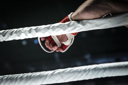 close-up de hand van de vechter MMA in de handschoen legt touwen van de ring