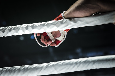 kickboxing: closeup hand of fighter MMA in glove lays ropes of ring Stock Photo