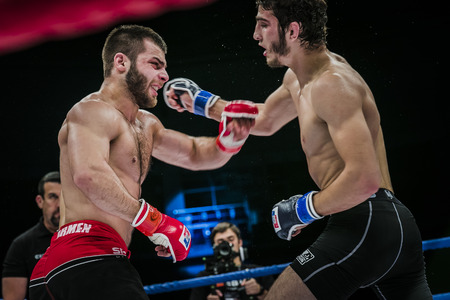 opponent: Chelyabinsk, Russia - December 5, 2015: athlete mixed martial arts fighter gets cross hand to his opponent during Cup of Russia MMA