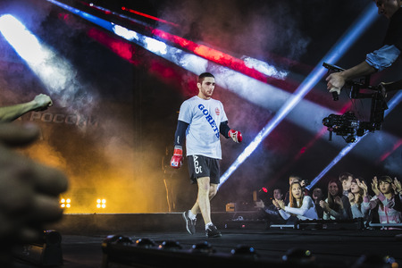 mma: Chelyabinsk, Russia - December 5, 2015: athlete mixed martial arts fighter is catwalk surrounded by fans. fans greet him. light and smoke during Cup of Russia MMA
