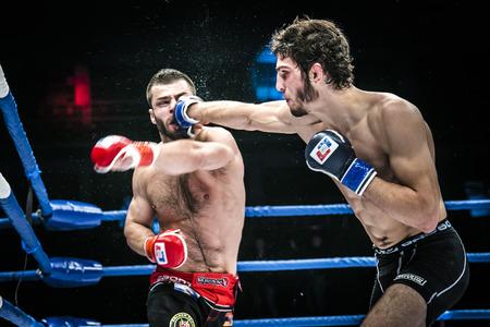 sudando: Chelyabinsk, Rusia - 5 diciembre 2015: batalla final luchadores de MMA patada mano a la cabeza. salpicaduras de agua y el sudor durante la Copa de Rusia MMA