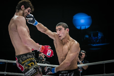 opponent: Chelyabinsk, Russia - December 5, 2015: mixed martial arts fighter gets jab hand to head of his opponent during Cup of Russia MMA