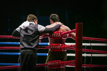 luchador de artes marciales mixtas (MMA) se encuentra en el anillo de esquina junto a él entrenador. romper entre las rondas en la lucha Foto de archivo