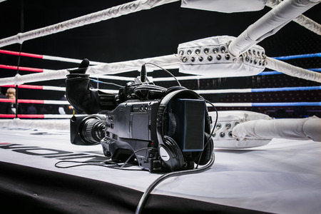 professional camcorder stands on corner ring for mixed martial arts. live broadcast competition in MMA and Boxing