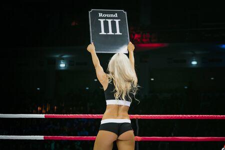 schöne sexy Mädchen während des Wettkampfes in MMA und Boxen in Ring. in seinen Händen zu unterzeichnen, mit runde Zahl